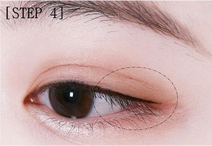 步骤三:接着用大地色眼影沿着刚才的白色眼影涂满