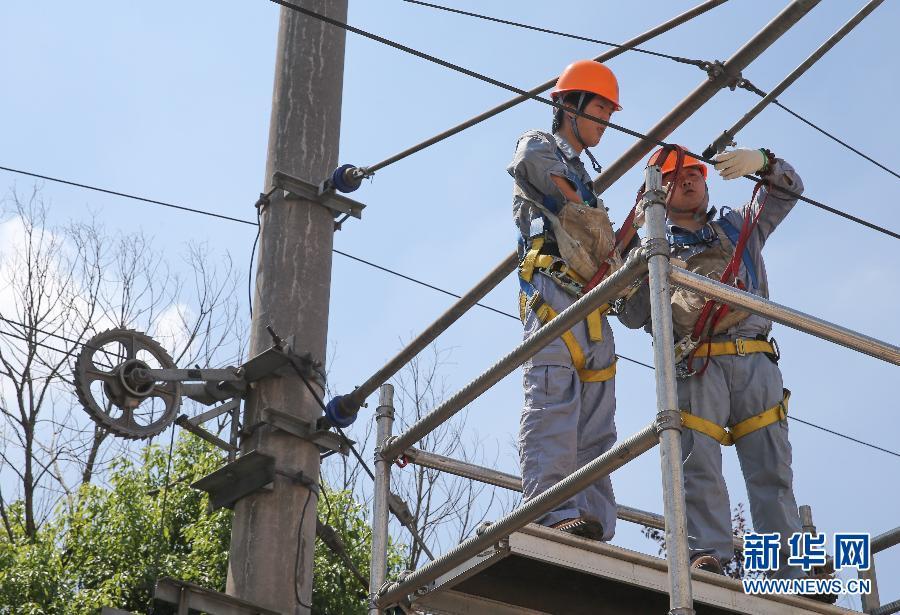 上海地铁一号线供电系统维护员薛神龙(右)和张雨峰在烈日下检查线路