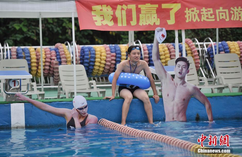 一市民坐在中国游泳运动员的照片旁。 陈超 摄   8月10日,重庆洋人街一游泳池挂起孙杨、宁泽涛等中国游泳名将的照片,鼓励前来游泳健身的市民向游泳冠军学习。图为游泳池挂起孙杨、宁泽涛等中国游泳队运动员的照片。陈超摄