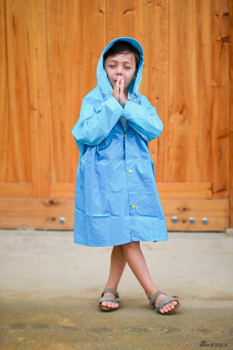 照片中诺一身穿蓝色雨衣,站在室外,表情阳光可爱!