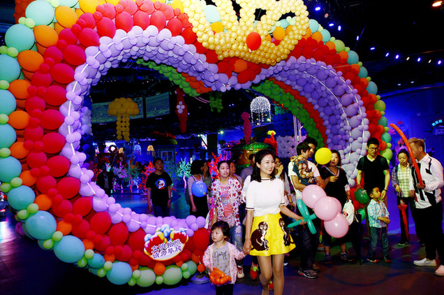 图为一位游客(左二)在气球嘉年华会上配合工作人员进行气球造型展示。  5月28日,一场海洋主题的气球嘉年华会在上海欢乐谷举行,五彩缤纷的气球组成各种海洋生物造型,吸引众多游客前来游玩,在超过一万平米近百万只气球组成的气球海洋中尽情欢乐。新华社记者 方喆 摄