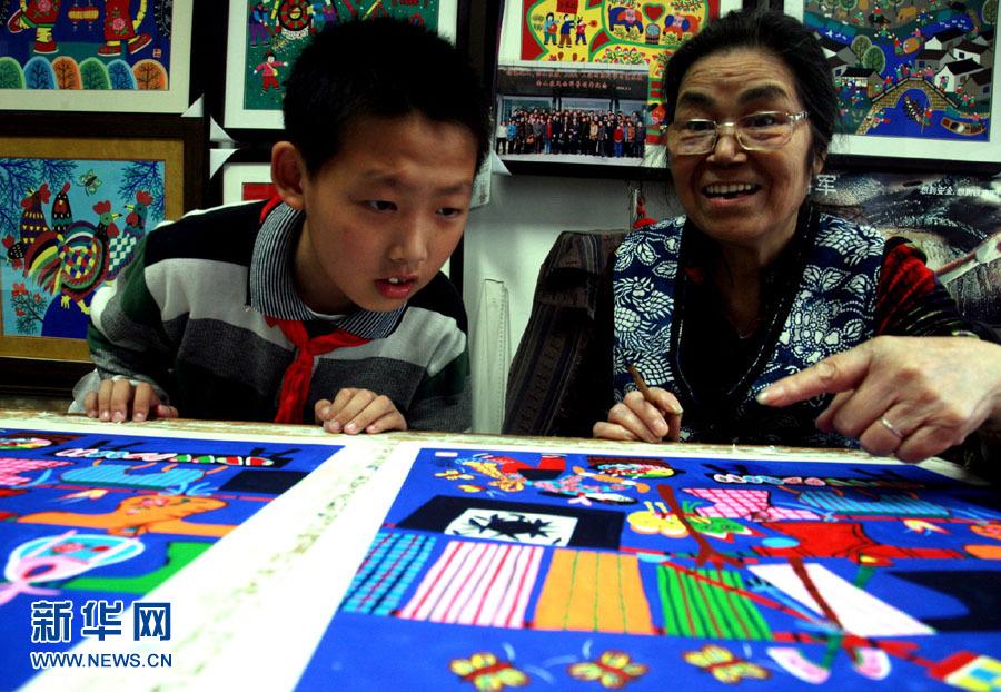 古稀的上海金山农民画院的农民画家张婉英向小学生介绍金山农民画